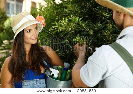 Happy young woman smiling in the garden, looking at gardener cutting the bush by secateurs.