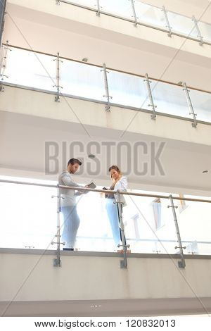 Business partners talking in corridor of multi-storey building.