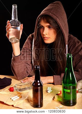 Drunk girl in hood keeps bottle of alcohol. Soccial issue alcoholism.
