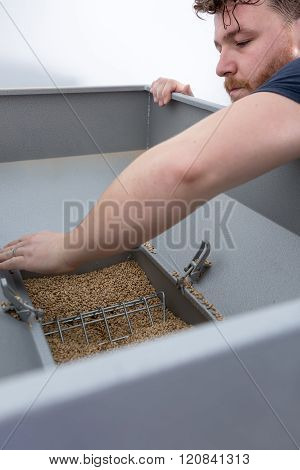 Man Opens Container With Malt Seeds
