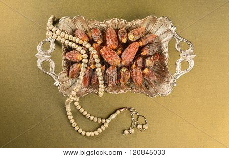 Dates - Ramadan food. Dates in a large siver tray with an Islamic rosary.