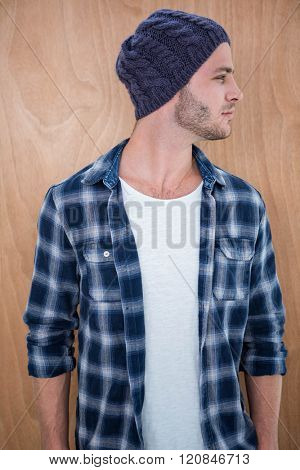Handsome hipster wearing a beanie hat on a wooden background