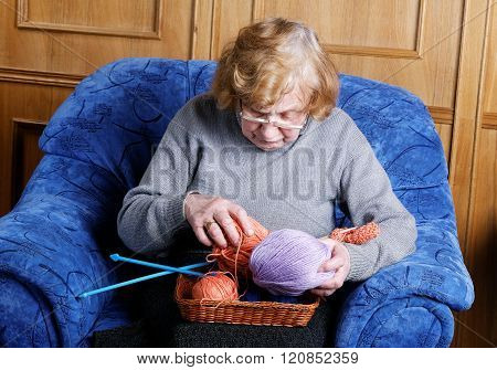 Grandmother In A Chair With A Thread For Knitting
