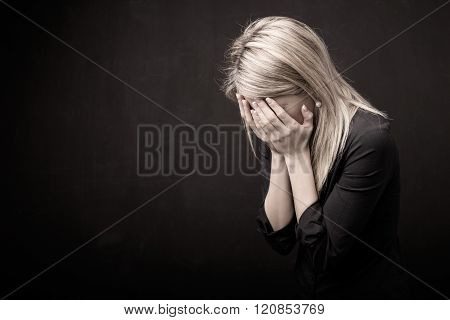 Woman holding her face in her hands