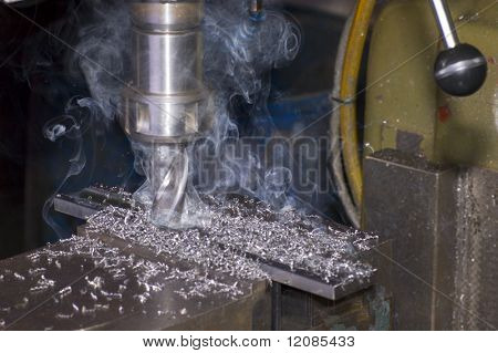 Milling machine is cutting metal with lot of smoke