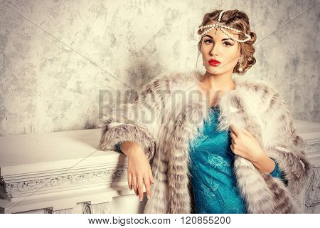 Stunning young woman wearing evening dress and beautiful furs. Luxury, rich lifestyle. Jewellery. Fashion shot. Interior in classical style.