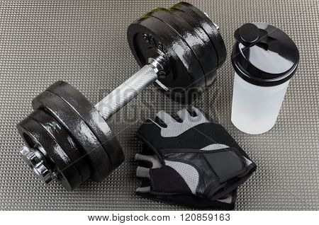 Ajustable Dumbbells, Training Gloves And Shaker On Mat