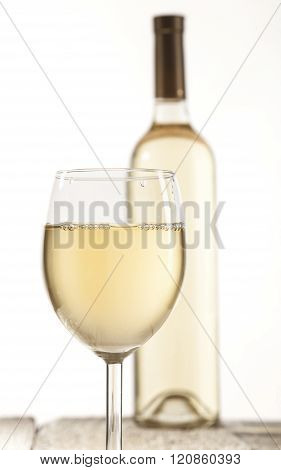 Wineglass and bottle with white wine on wooden table and white background