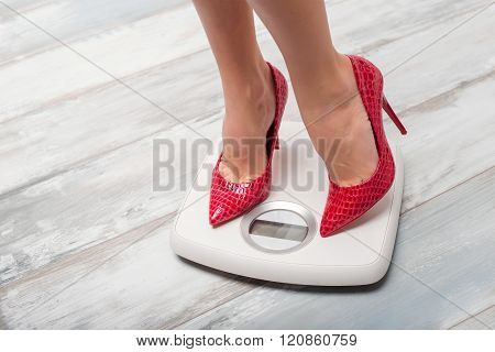 Woman with red high heels on weight scale