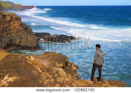 GRIS-GRIS, MAURITIUS ISLAND - 1. NOVEMBER, 2015: Unidentified tourist on sea cliff where the constant squashing of waves against the flanks of the cliff gives the impression that the cliff is crying.