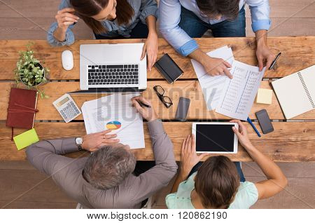 High angle view of businesspeople analyzing schemes and diagrams. Business team analyze growth of company. Businesspeople in meeting discussing future prospects and growth strategies in office.