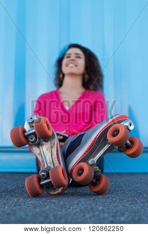 Happy young woman sitting on ground wearing rollerskates. Young beautiful woman leaning against blue wall and thinking about a good event. Young woman is feeling satisfied after practicing.