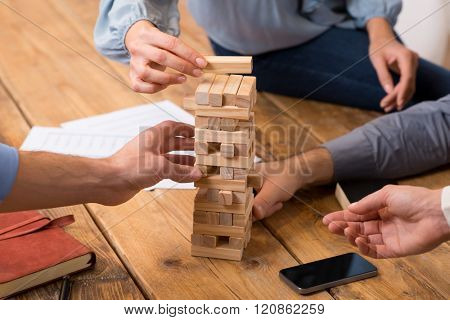 Close up of hands helping build a building of wooden pieces. Businesspeople planning a new business strategy. Business team trying to generate new ideas with wooden bricks. Business risk concept.