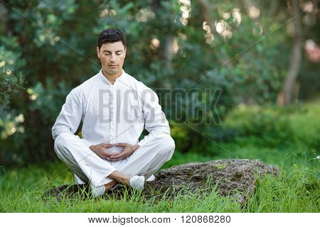 Man Doing Meditation Sitting On The Stone Outdoors