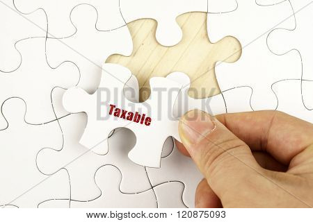 Finance Concept. Hand Holding Piece Of Jigsaw Puzzle Showing Taxable Word.