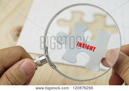 Hands holding magnifying glass and piece of jigsaw puzzle.