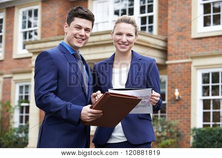 Male And Female Realtor Standing Outside Residential Property