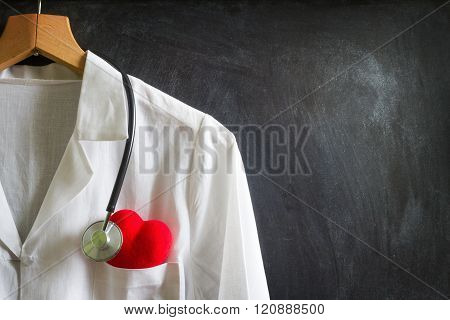 Doctor coat with stethoscope on blackboard abstract background