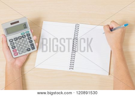 Hand Holding Calculator And Writting On Notebook