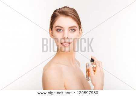 Beauty portrait of pretty young woman holding bottle of parfume over white background