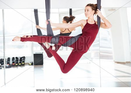 Concentrated beautiful young woman practicing different antigravity yoga positions over the mirror