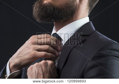 Bearded businessman in suit tying up his tie.