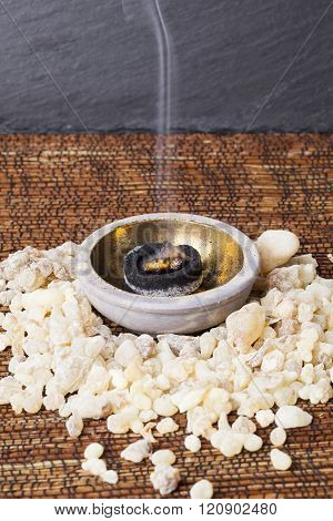 Frankincense burning on a hot coal. Frankincense is an aromatic resin, used for religious rites, incense and perfumes.