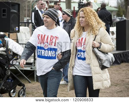 MAR 5, 2016 - WOODBRIDGE, NJ: A couple wearing New Jersey Transit rail workers union tshirts with the slogan SMART and Strong walk away from the stage after the rally to support the rail labor unions.
