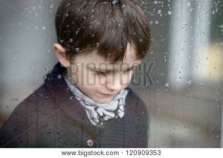 Sad Depressed 7 Year Old Boy Standing By The Window