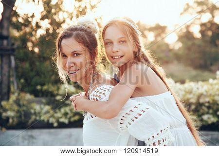 Tween daughter hugging with her mom in summer sunlight
