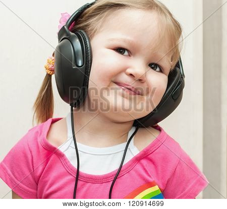Little Beautiful Girl In Headphones Listens To Music