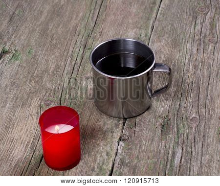 The Burning Red Candle And Steel Cup Of Coffee