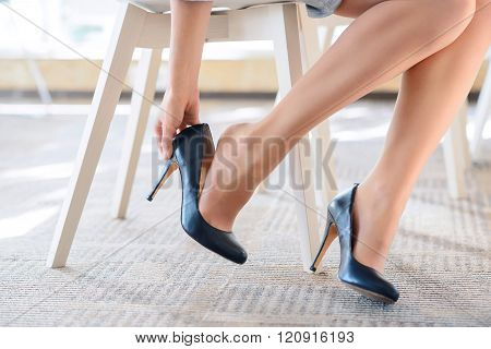Pleasant woman putting  her shoes off