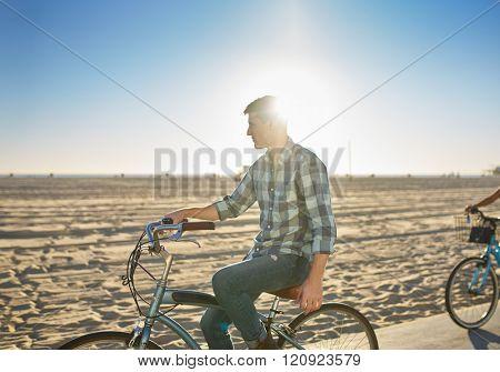 man riding bicyle on santa monica beach