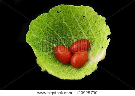 three tomatoes in a savoy leaf on black