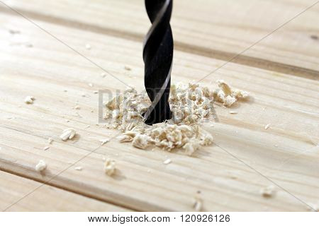 a wood drill pierced into a wooden board