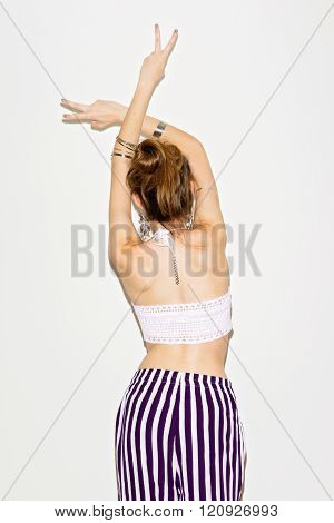 Hippie boho young woman in crochet top and striped pants gesturing peace