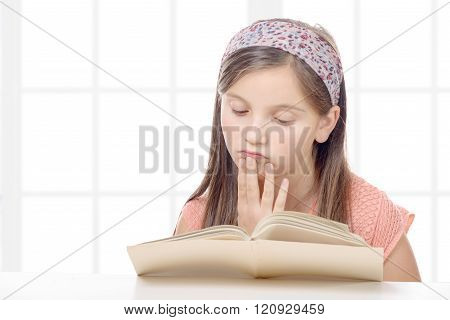 preteen girl reads a book