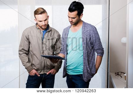 Focused gay couple looking at tablet at home
