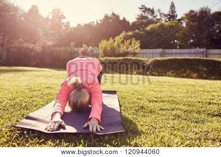 Woman in yoga pose on mat outdoors with sunflare