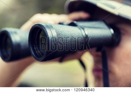 hunting, war, army and people concept - close up of young soldier, ranger or hunter with binocular observing forest poster