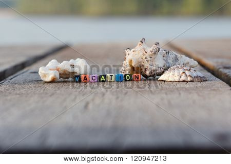 Word VACATION on colourful dices and sea shells on wooden table with sea and faraway trees in the ba