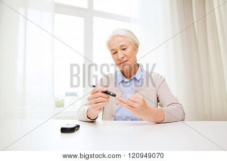 medicine, age, diabetes, health care and people concept - happy senior woman with glucometer checking blood sugar level at home