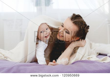 Happy family,mother playing with her baby in the bedroom.