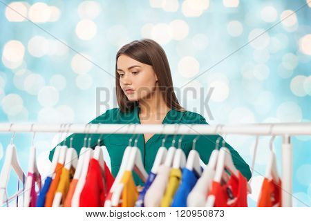 nothing to wear, clothing, fashion and style concept - woman choosing clothes at wardrobe over blue holidays lights background