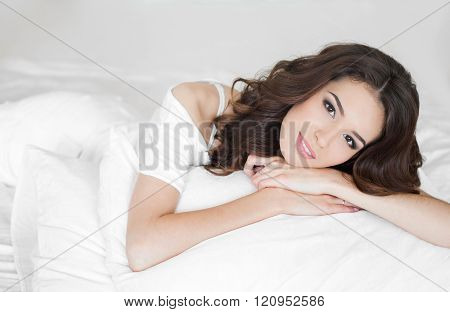 Happy young woman wakes up in a white bed in the morning
