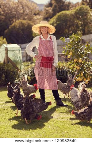 Senior woman standing proudly with her healthy free range chicke