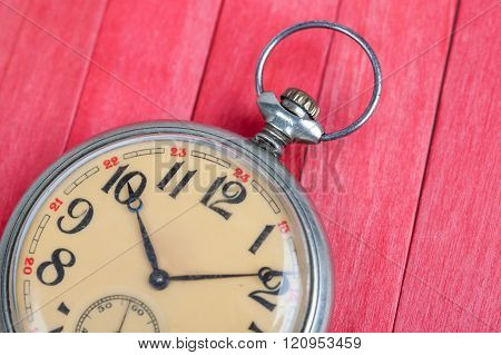 Close Up Of Old Style Pocket Watch On Red Wooden Backround