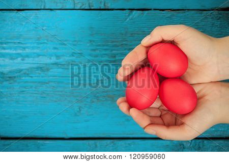 Red easter eggs in the hands