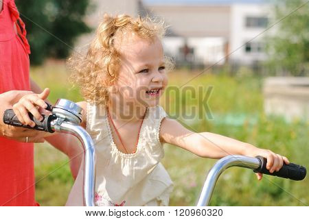 Little Girl Sitting On The Bike And Hold The Wheel